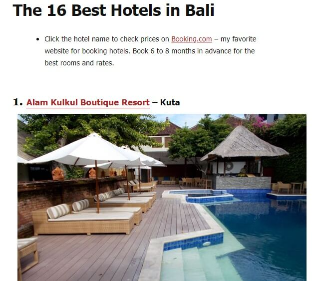 This image shows a swimming pool with sun beds and white umbrellas in the hotel named Alam Kulkul Boutique Resort